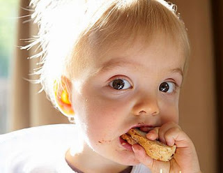 Baby boy eating a slice of bread